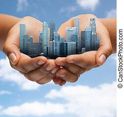 hands holding city over blue sky background