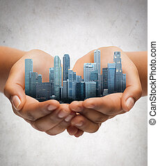 hands holding city over gray concrete background