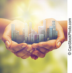 hands holding city over green natural background