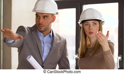 architects with blueprint and helmets at office -...