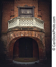 Architecture details, the front door with the balcony of the Hunting Castle at Manuc Bei mansion, Moldova. Old brick building facade. Halloween haunted house concept, ghost home.