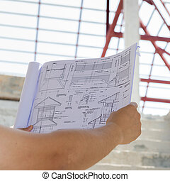 architecture drawings in hand on house building background