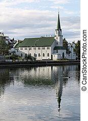 Architecture in Reykjavik, Iceland. Church next to lake Tjornin.