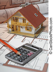architectural model house on blue print plan with financial calculator
