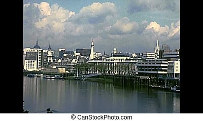 London Bridge with warship on river Thame. boats docked in Westminster district. Archival of London city of England, United Kingdom in the 1970s.