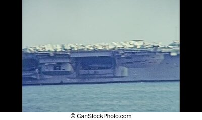 Panoramic view of USS Nimitz (CVN-68) carrier warships of United States Navy, made in 1975. Navigating in the port of Genova city in 1981. Archival of Italy in the 1980s with Genova Italian harbor.