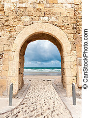 Archway in a fortification leading to a sandy beach