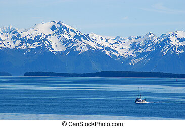 Alaska mountain range towers over commercial fishing boat in the foreground