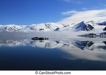 Arctic Wonderland - Snow covered mountain and reflection in...