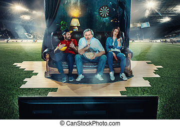Ardent fans are sitting on the sofa and watching TV in the middle of a football field.