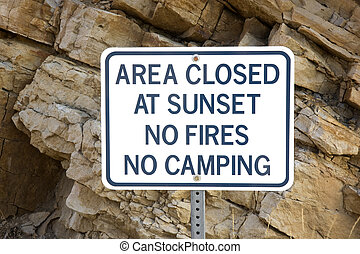 area closed at sunset - warning sign