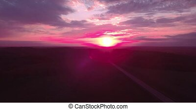 Areial view of a long straight road and a colorful sky at...