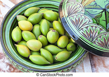 Argan nuts in a green plate.