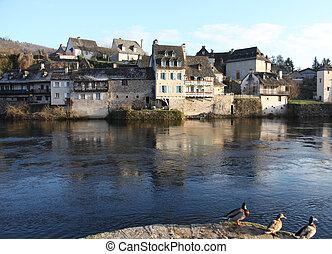 Riverside stone houses In Argentat along the dordogne river in France