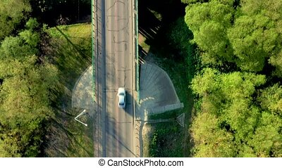 Arial view of white car moving on rural road through village.