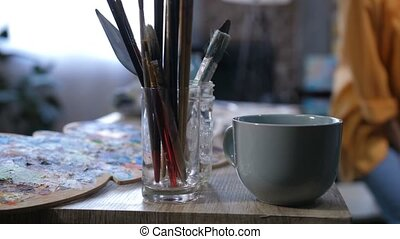 Aristic tools and cup of hot drink on work table - Close-up...