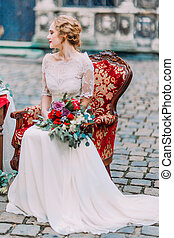 Aristocratic blonde bride with wedding bouquet in hands sitting on red vintage armchair