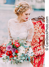 Aristocratic bride with blonde curly hair sits on vintage armchair and enjoy the moment