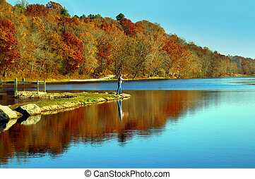 Lone fisherman casts his line into small lake in northern Arkansas. Early morning light reflects blue into lake's glassy surface and fall foliage adds reds and golds.