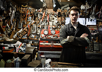 Arm Crossed Worker in a Shed and Lots of Tools Hanging
