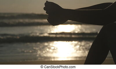 Arm of young woman playing with sand. Female hand pouring sea sand through her fingers at sunset against an ocean background. Slow motion Close up