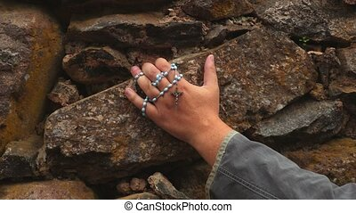 Arm with rosary on stone wall