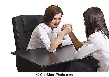 Arm wrestling - Businesswomen arm wrestling against a white...
