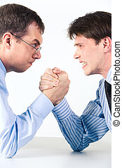 Conceptual photo of business competition: two businessmen wrestling with aggressive expression on their faces