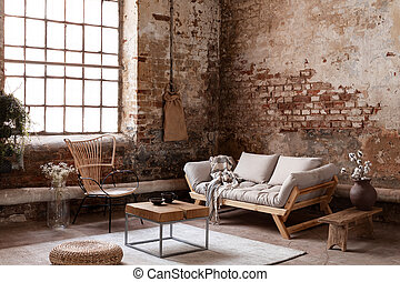 Armchair and beige sofa in industrial living room interior with wooden table, pouf and window. Real photo