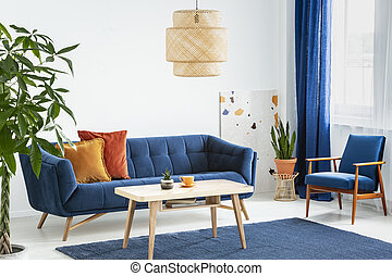 Armchair and sofa in blue and orange living room interior with lamp above wooden table. Real photo