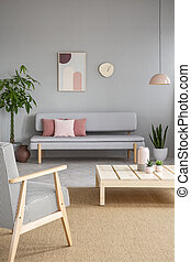 Armchair and wooden table in grey living room interior with poster and clock above sofa. Real photo