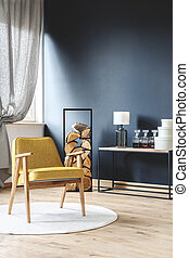 Armchair in a room with black wall