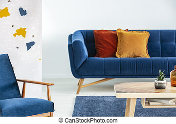 Armchair next to wooden table and blue sofa with pillows in modern living room interior. Real photo