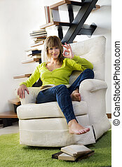 armchair - Portrait of young woman relaxing in chair at home