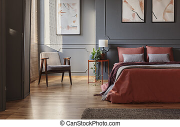 Armchair standing in a corner next a double bed with ginger sheets in a bedroom interior with paintings