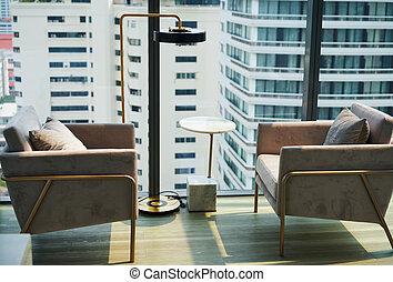 Armchairs near big window with city view