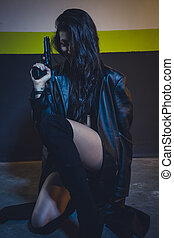 Armed and dangerous brunette girl with a gun and a machine-gun in a garage at night
