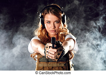 Armed blonde woman shoots with gun at a target in the darkness with smoke clouds