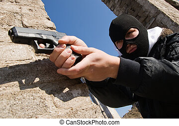 Armed criminal aiming with a pistol