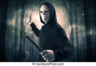 Armed hitman in dark nocturnal forest concept