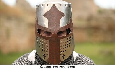 armed knight with in helmet looking in camera