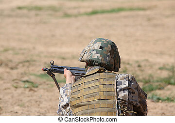 armed man in camouflage with rifle in hands