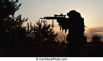 Armed man taking aim at sunset. Airsoft - Armed man taking...