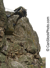 Armed military alpinist climbing