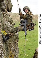 Armed military alpinist hanging on rope