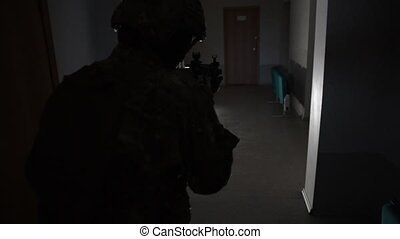 armed with m4 military inspects a dark room