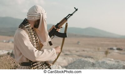 Armed mujahid in the field - Armed mujahid shooting from the...