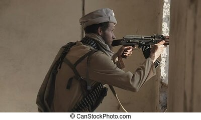 Armed mujahid with the clip over clothes fires his rifle out...