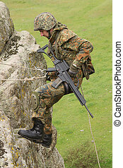 Armed soldier does alpinism - Military man does dangerous ...