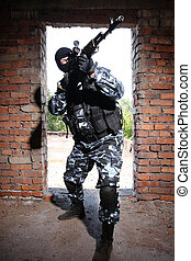 Armed soldier in black mask targeting with a gun